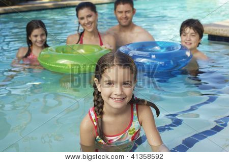 Portrait of a cute preadolescent girl in swimming pool smiling with family in the background