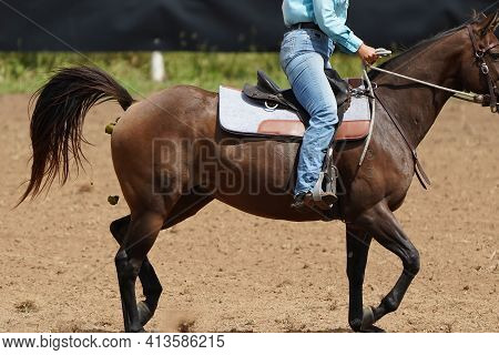Close Up Of A Horse And Its Manure As It Trots Along Being Ridden By A Cowgirl
