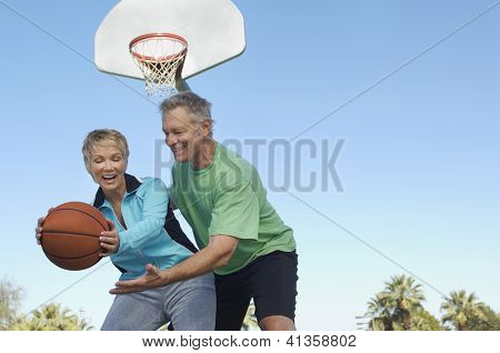Low angle view of a happy couple playing basketball together at court