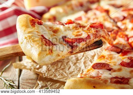 Spicy Sausage Italian Pizza with tomato, mozzarella cheese, sausage slice. Homemade pizza on baking paper with food ingredients on wooden table. Pizza slice closeup view