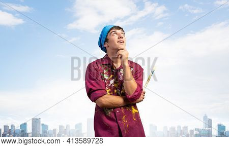 Pensive Painter Artist Standing With Folded Arms On Modern Cityscape Background. Portrait Of Young M