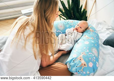 A Beautiful Young Mother With Long Blonde Hair And A Daughter Of 2-3 Months Are Resting On The Bed W
