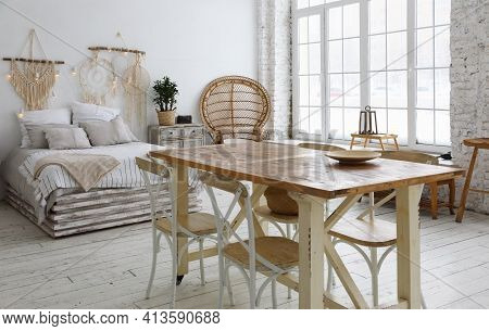 The Interior Of A Large Modern Living Room With A Dining Table, A Bed  And Large Windows Flooded Wit