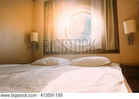 Natural Sunlight Shining Through Ship Window In Craft Cabin With Bed. View On Sea. Luxury Cabin On F