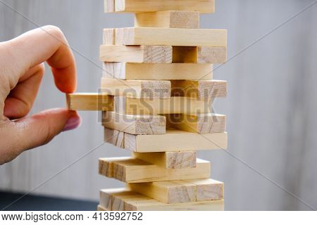 Building From Wooden Blocks. Game For Family Of Wooden Bars. Wood Blocks Stack Game With Hand On Bac
