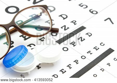 Contact Lenses Case And Eye Glasses On And Eye Test Chart. Vision Concept. Way To Improve Vision. Cl