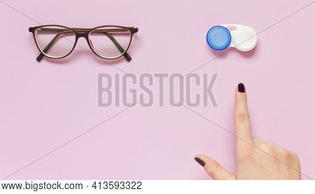 Glasses And Contact Lens Case On Purple Background. Human Hand Indicate On Lenses. Concept Of Choice