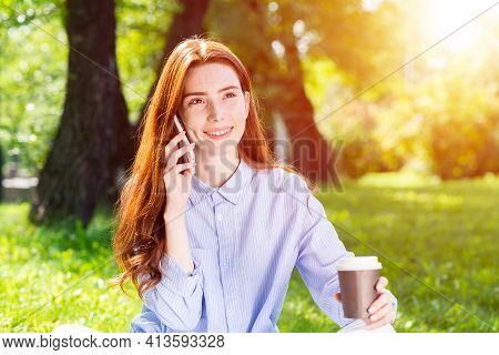 Young Redhead Woman Talking On Smartphone In Summer Park. Beautiful Girl Relaxing Outdoors On Sunny