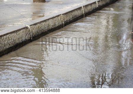 Blurred Motion, Stream Of Rainwater On The Road. Wide Muddy Water Stream At The Curbs. City Street A