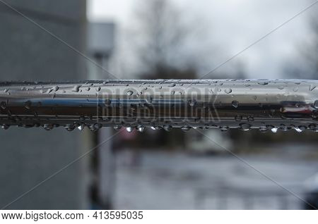 Raindrops On A Metal Railing Close-up. Wet Metal Railing Outdoors. Blurred Background. Selective Foc