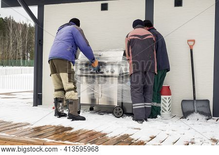Group Of People Unwrapping A Brand New Household Appliance, Winter Scene