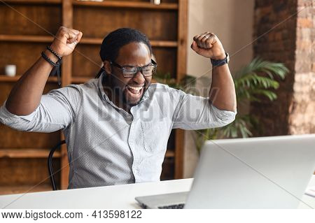 Excited Lucky African American Businessman Or Office Manager Sitting With A Laptop At The Desk, Rais