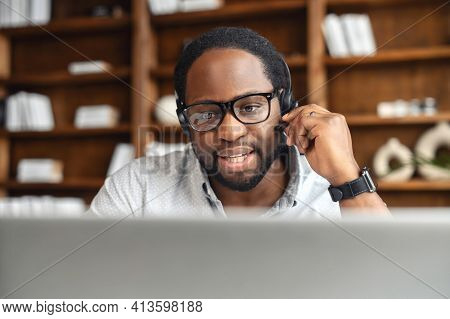 Young African American Male Office Worker In Glasses And Headset Answering The Phone Call, Looking A
