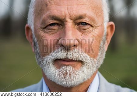 Close Up Portrait Of Senior Man. Elderly Man With Wrinkled Face Is Looking At Camera.