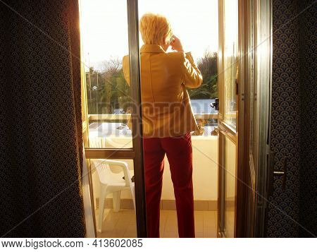 Woman Standing On A Balcony At Sunset, Overnight Stay In Tourism