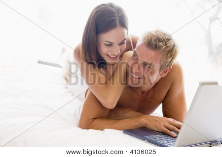 Couples Lying In Bed With Laptop Smiling