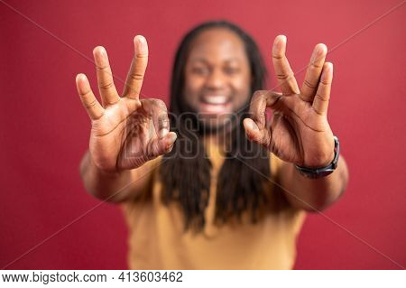 African American Man With Dreadlocks Isolated On Red Wall Looking At Camera, Showing Okay Sign With