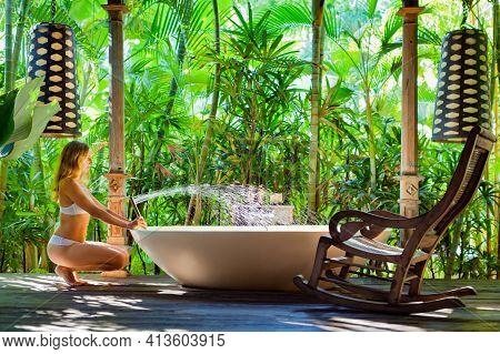 Happy Young Woman Have Fun In Open Air Bathtub. Joyful Girl Take Bath In Outside Bathroom On Veranda