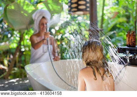 Happy Baby Girl With Mother Have Fun In Bath. Playful Woman Spraying Child From Shower In Outside Ba