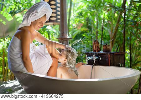 Happy Baby Girl, Mother Have Fun In Bath. Young Woman Soaping By Shampoo Child Head In Outside Bathr