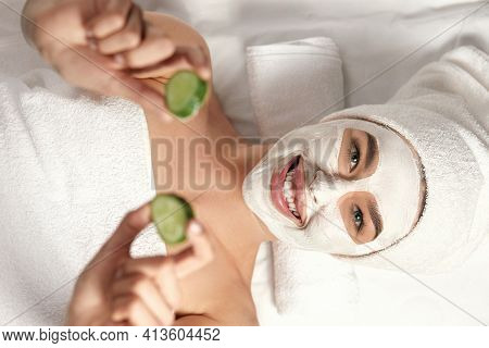 Spa. Beautiful Woman With A Clay Mask On Her Face And Cucumbers In Hands . Face Peeling Mask. Skin C