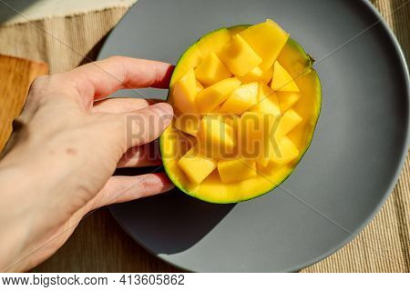 Healthy Morning Breakfast. Hand Holds A Mango. Bright Yellow Mango In A Plate. Exotic Fruits On A Pl