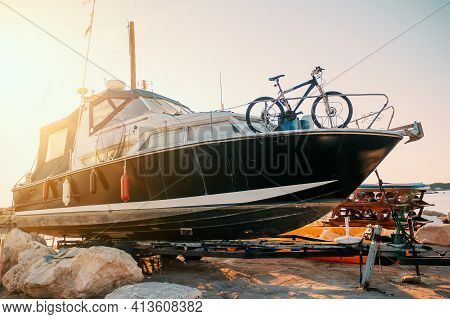 Boat Cabin Motorboat Cruiser Yacht On Shore Ready For Maintenance And Transportation.