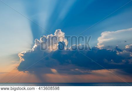 Magnificent Sunset Over Sea. Sun Covered By Picturesque Cloud With Beautiful Shine Sun Beams In Sky.