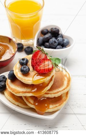 Healthy breakfast with pancakes and orange juice. Homemade american pancakes with berries and honey