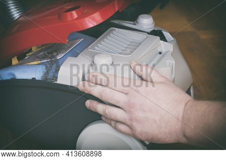 Man's Hand On A Red Open Vacuum Cleaner And Inside An Overflowing Dust And Dirt Bag