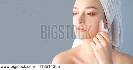 Guasha Face Massage. Beauty Banner. Alternative Skincare. Woman With Nude Makeup Bare Shoulders Towe