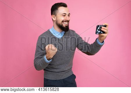 Shot Of Happy Handsome Young Brunette Unshaven Man With Beard Wearing Everyday Grey Sweater And Blue