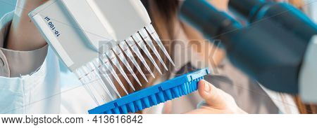 student woman in genetic laboratory with multi pipette and other PCR items in microbiological  genetic laboratory