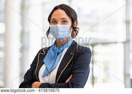 Portrait of flight attendant standing at airport terminal wearing face mask for safety against covid-19. Stewardess with surgical mask looking at camera, aircrafts are waiting and preparing flight.