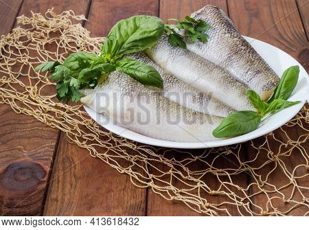 Raw Carcasses Of The Notothenia Fish Without Of Heads And Tails And Twigs Of Greens On Dish On A Rus