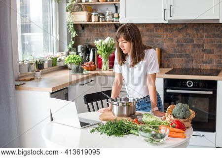Close Up Woman In White T-shirt Cooking Soup With Fresh Vegetables In Kitchen At Home. Menu, Recipe