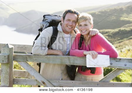 Couples On Cliffside Outdoors Leaning On Railing And Smiling