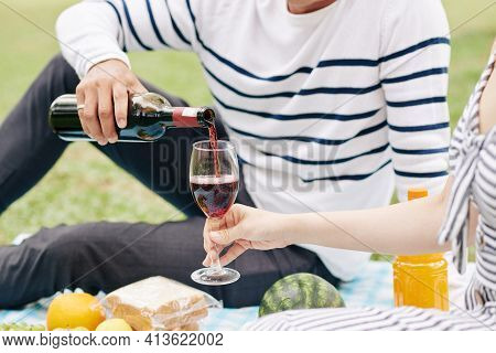 Cropped Image Of Young Man Pouring Red Wine In Glass Of Girlfriend When They Are Enjoying Picnic In