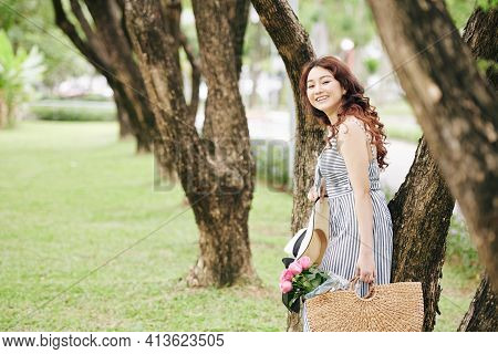 Portrait Of Lovely Young Asian Woman In Summer Dress Standing In City Park With Hat And Wicker Bag O