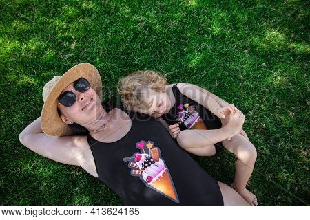 Mom And A Little Girl In Identical Swimsuits Are Resting In The Summer Lying On The Grass In The Sha