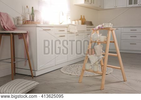 Decorative Ladder With Different Dishware And Field Flowers Bouquet In Stylish Kitchen. Idea For Int