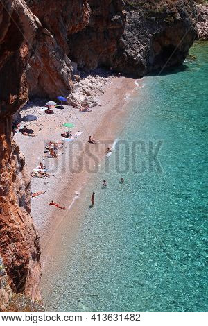 Konavle, Croatia - June 28, 2019: People Spend Vacation At Pasjaca Beach Below Cliffs In Konavle Reg