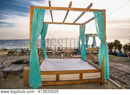 Alanya, Turkey -October 20, 2020: Luxury wood framed whit  curtains for relaxing on the sandy Cleopatra beach in Alanya,  Turkey.