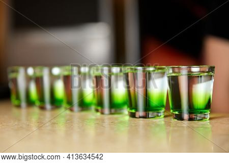 Several White-green Alcoholic Drinks Shots On The Bar Counter