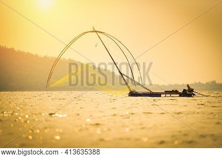 Asia Fisherman Net Using On Wooden Boat Casting Net Sunset Or Sunrise In The River - Silhouette Fish