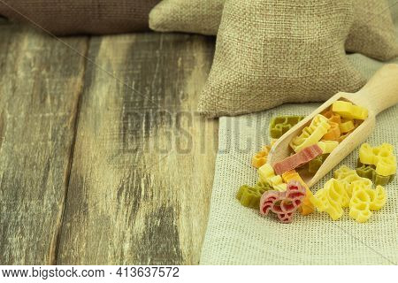 Raw Pasta Of Different Colors In A Wooden Spoon. Pasta On The Background Of A Wooden Shield With Spa