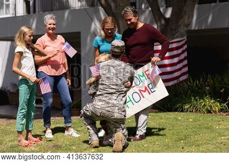 Caucasian soldier father greeting family with welcome sign and american flags outside home. soldier returning home to family.