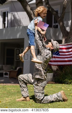 Smiling caucasian soldier father lifting happy son in garden with american flag outside house. soldier returning home to family.