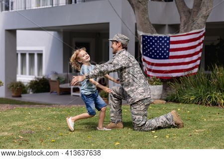 Smiling caucasian soldier father greeting happy son in garden with american flag outside house. soldier returning home to family.