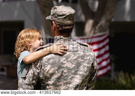 Rear view of caucasian soldier father carrying son in garden with american flag outside house. soldier returning home to family.